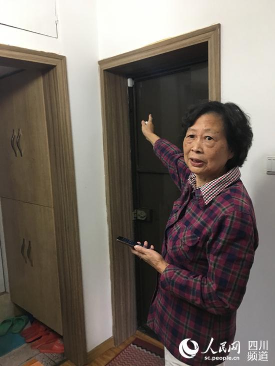 71岁的万天禄老人家介绍着家里门口处安装的安防设备。