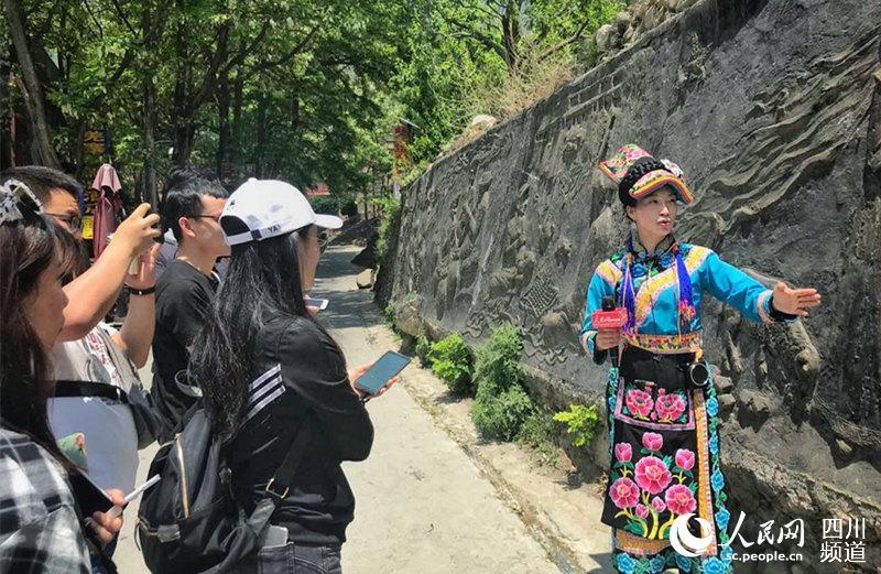 图为张泽利为媒体介绍村里的旅游产业。 (郭洪兴 摄)