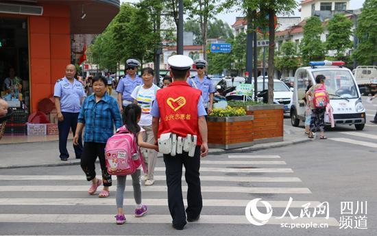 网友收集照片(交通志愿者带小孩过马路)