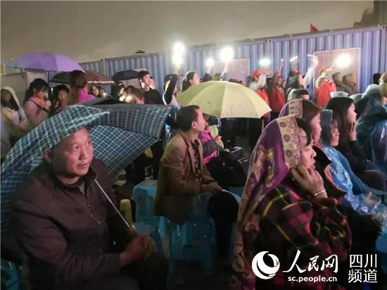现场工友打着伞、穿着雨衣观看演出。